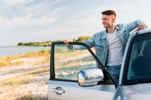 Mittlerer schuss smiley-mann, der mit auto aufwirft