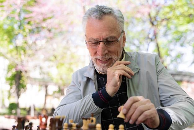 Mittlerer schuss smiley-mann, der schach spielt playing