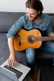 Mittlerer schuss smiley-mann mit gitarre und laptop