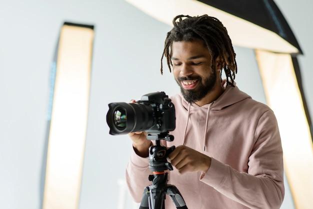 Mittlerer schuss smiley-mann mit kamera