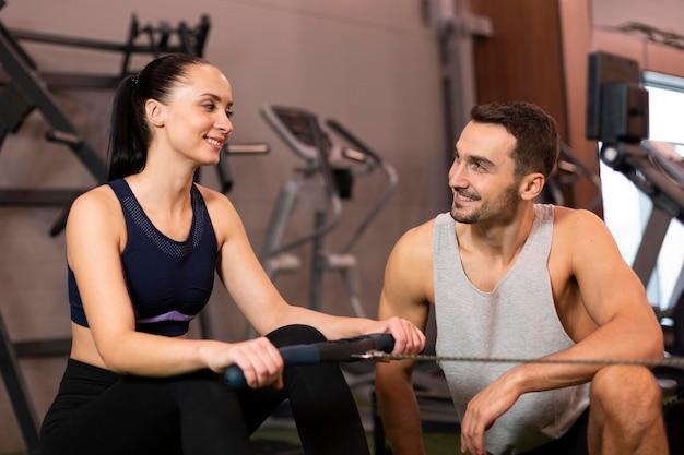 Mittlerer schuss smiley mann und frau im fitnessstudio