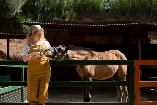 Mittlerer schuss smileyfrau, die pferd füttert