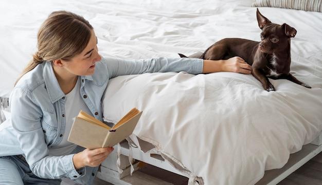 Mittlerer schuss teenager, der mit hund liest