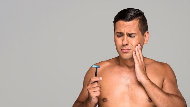 Mittlerer schuss trauriger mann, der rasiermesser hält