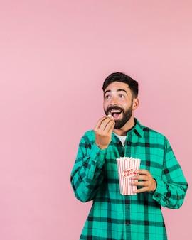 Mittlerer schuss überraschter kerl, der popcorn isst