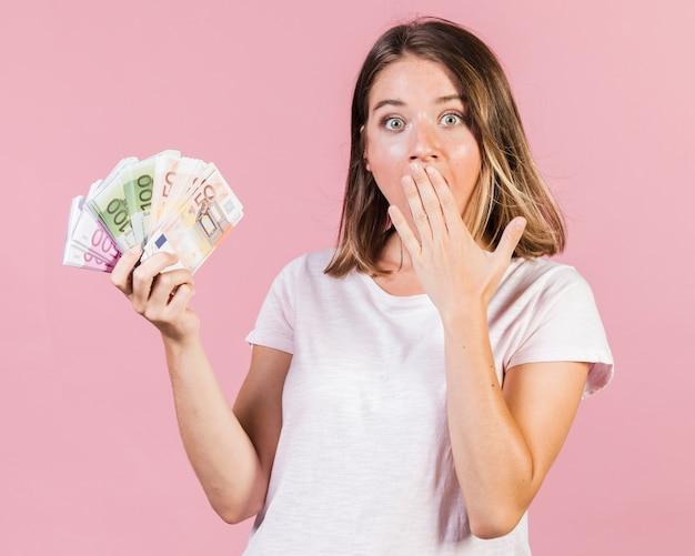 Mittlerer schuss überraschtes mädchen, das geld hält