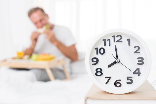 Mittlerer schuss unscharfer mann, der morgens frühstückt