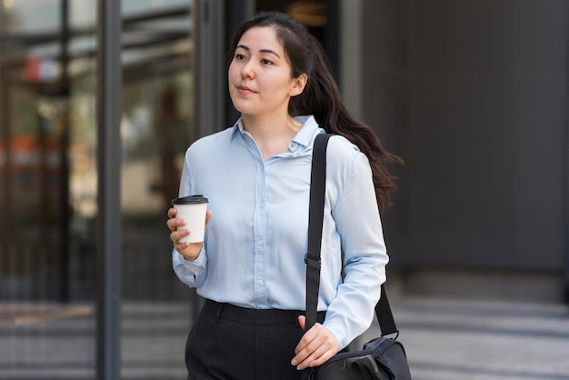 Mittlerer schuss unternehmer, der kaffee hält