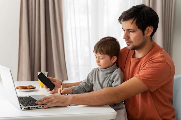 Mittlerer schuss vater, der fern mit kind arbeitet