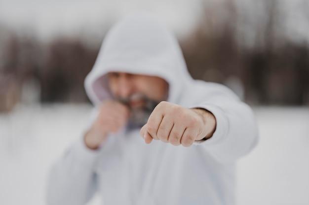 Mittlerer schuss verschwommener mann, der draußen trainiert