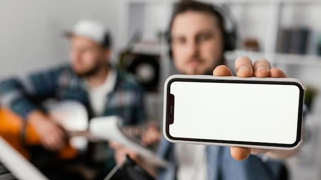 Mittlerer schuss verschwommener mann, der smartphone hält