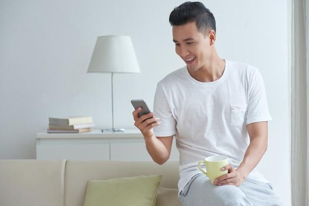 Mittlerer schuss von beschäftigtem sms des jungen darms in seinem social media auf smartphone morgens