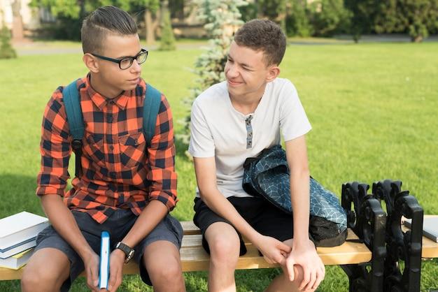 Mittlerer schuss von den highschool jungen, die auf bank sitzen