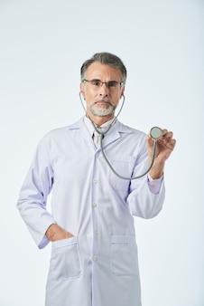 Mittlerer schuss von doktor kamera betrachtend und mit stethoskop gestikulierend, als ob den herzschlag überprüfend