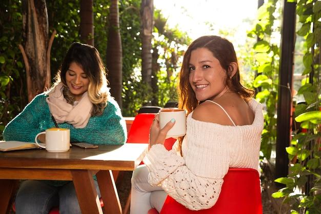 Mittlerer schuss von freunden an der kaffeestube
