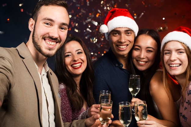 Mittlerer schuss von freunden an der party des neuen jahres mit champagnergläsern