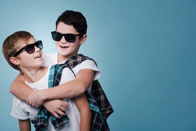 Mittlerer schuss von jungen mit der sonnenbrille, die mit kopienraum aufwirft