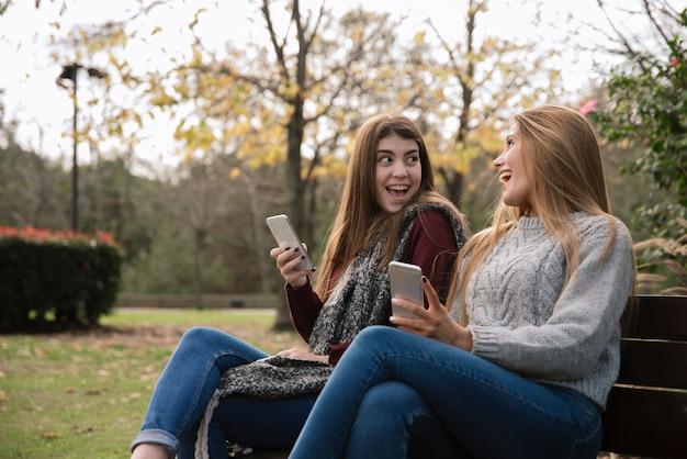Mittlerer schuss von zwei frauen, die im park mit telefonen sprechen