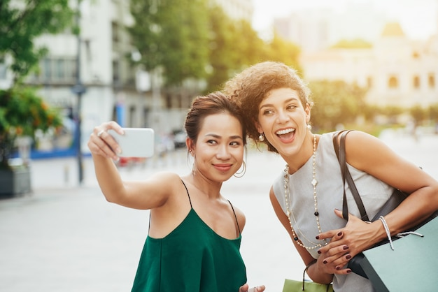 Mittlerer schuss von zwei freunden, die draußen selfie nehmen