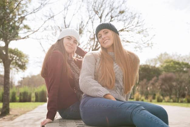 Mittlerer schuss von zwei lächelnden frauen, die auf einer bank sitzen