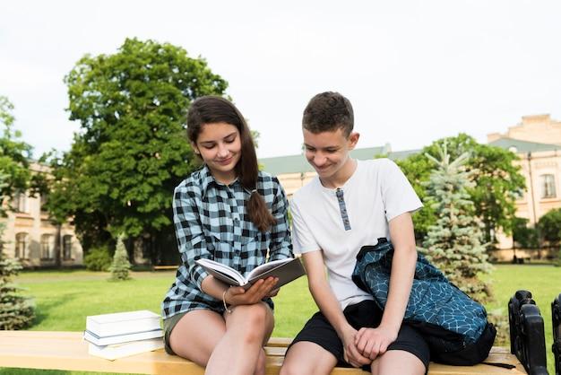 Mittlerer schuss von zwei lächelnden mitschülern, die anmerkungen teilen