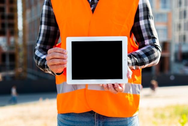 Mittlerer schussbauingenieur, der tablette hält
