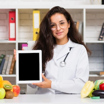 Mittlerer schussernährungswissenschaftler, der ein tablettenmodell hält