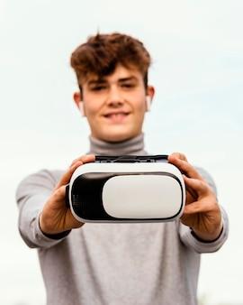Mittlerer schussjunge, der brille der virtuellen realität hält