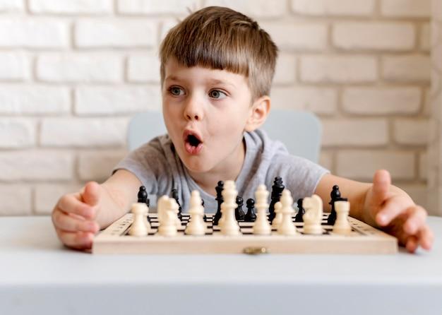 Mittlerer schussjunge, der schach spielt