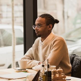 Mittlerer schussjunge mit brille, die an einem tisch sitzt