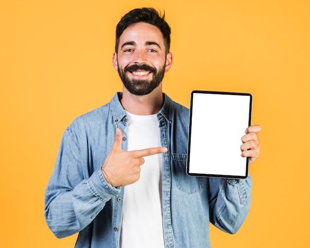 Mittlerer schusskerl, der auf eine tablette zeigt