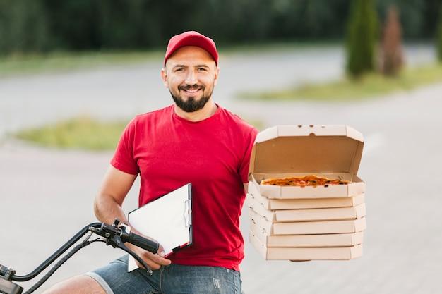 Mittlerer schusskerl, der pizzakästen und klemmbrett hält