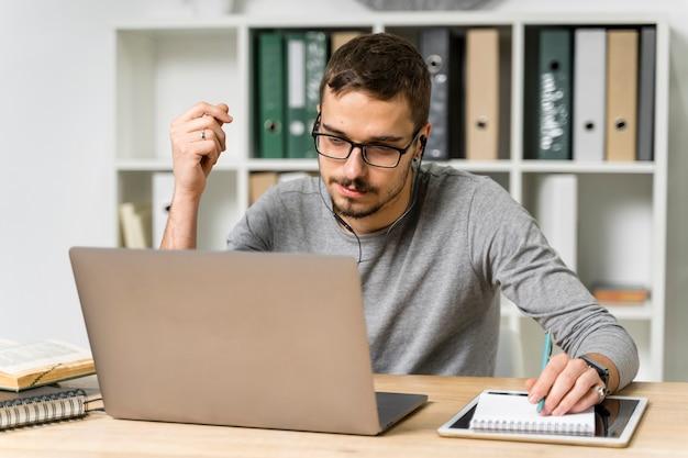 Mittlerer schusskerl mit den kopfhörern, die laptop betrachten