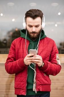 Mittlerer schusskerl mit den kopfhörern, die smartphone betrachten