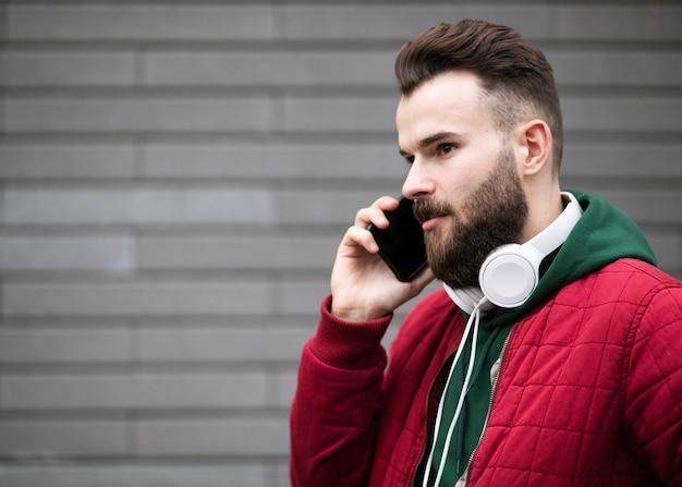 Mittlerer schusskerl mit kopfhörern sprechend am telefon