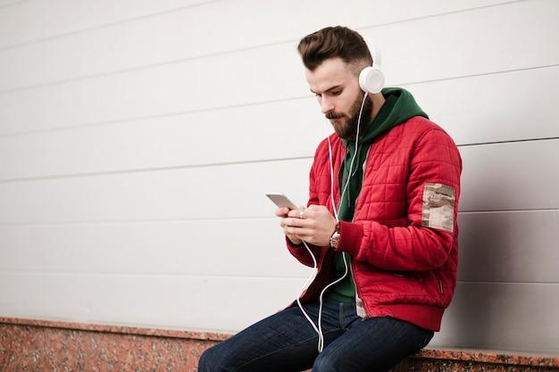 Mittlerer schusskerl mit kopfhörern und smartphone