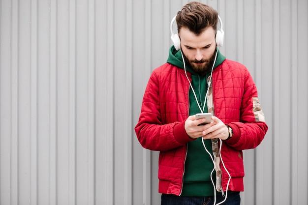 Mittlerer schusskerl mit smartphone und kopfhörern