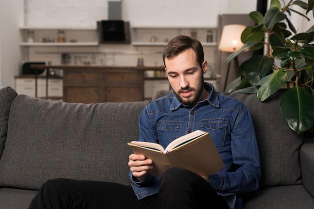 Mittlerer schussmann, der auf couch und lesebuch sitzt