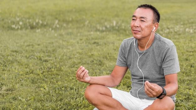 Mittlerer schussmann, der auf gras meditiert