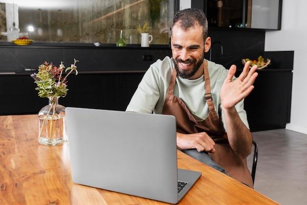 Mittlerer schussmann, der auf laptop winkt