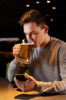 Mittlerer schussmann, der bier in der kneipe trinkt