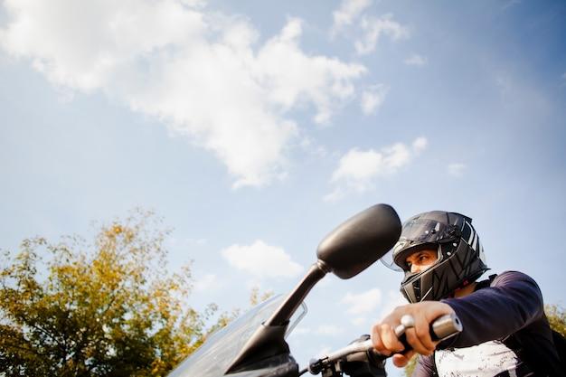 Mittlerer schussmann, der ein motorrad reitet