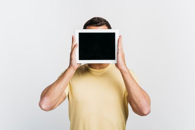 Mittlerer schussmann, der eine tablette vor seinem gesicht hält