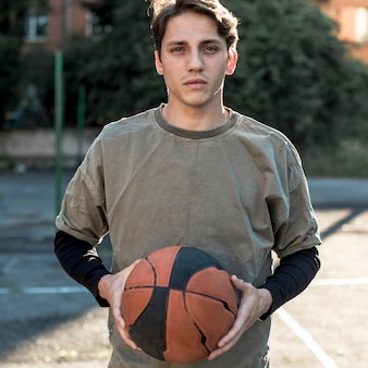 Mittlerer schussmann, der einen basketball hält