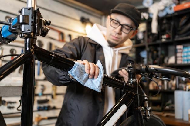Mittlerer schussmann, der fahrrad putzt