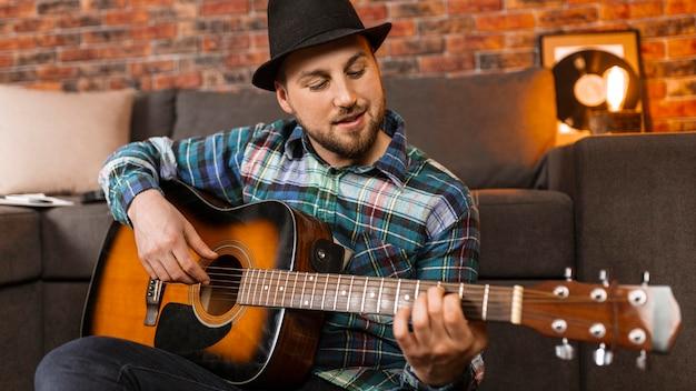 Mittlerer schussmann, der gitarre spielt Premium Fotos