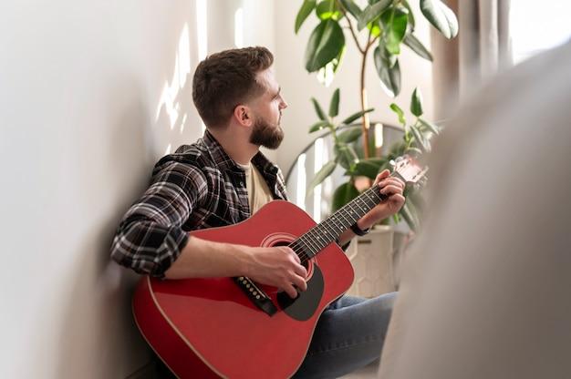 Mittlerer schussmann, der gitarre spielt