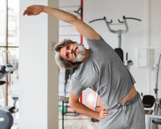 Mittlerer schussmann, der im fitnessstudio streckt