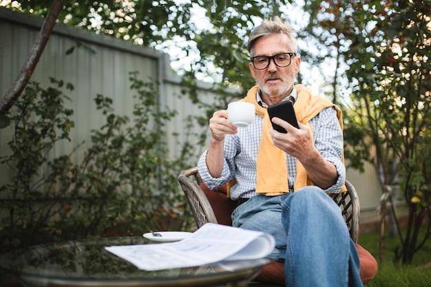 Mittlerer schussmann, der kaffee draußen trinkt