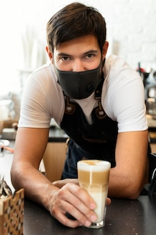 Mittlerer schussmann, der kaffeeglas hält